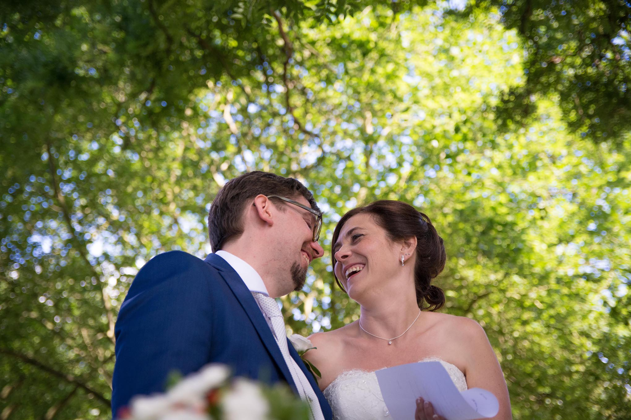 Verliefde bruidegom en bruid kijken elkaar aan onder een grote boom op hun trouwdag.