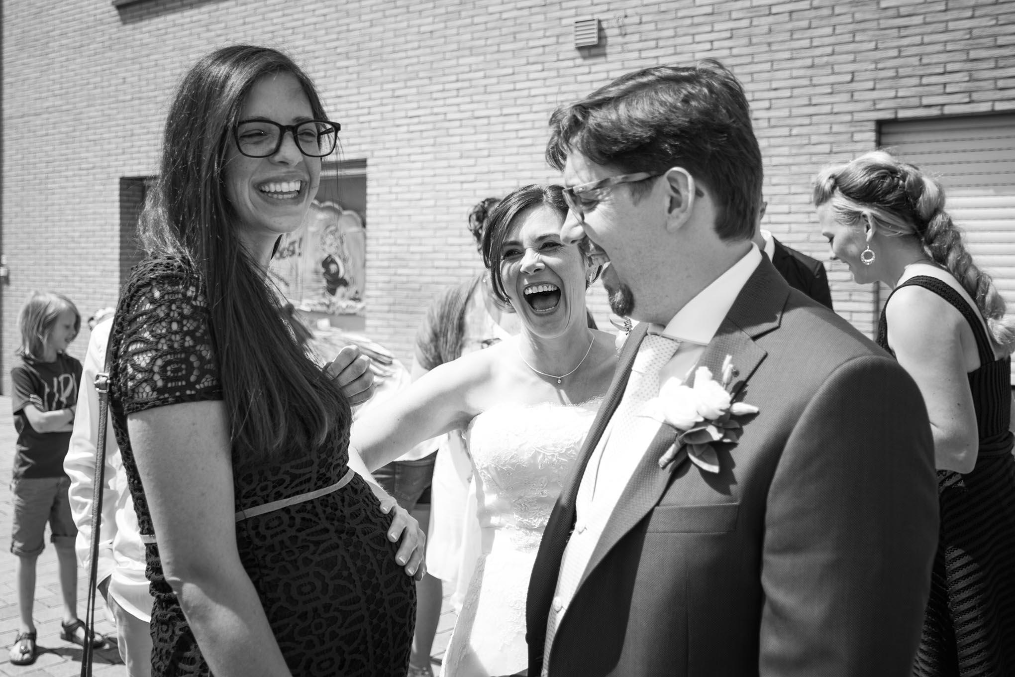 Bruid komt aan de zwangere buik van een vriendin op haar trouwdag, de bruid kijkt lachend toe.