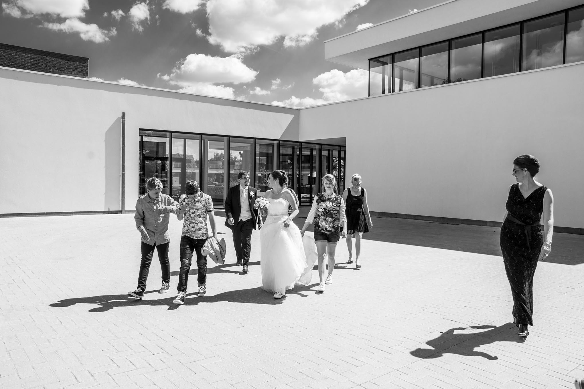 Bruid en bruidegom verlaten een rvt in Kortrijk samen met hun kinderen.