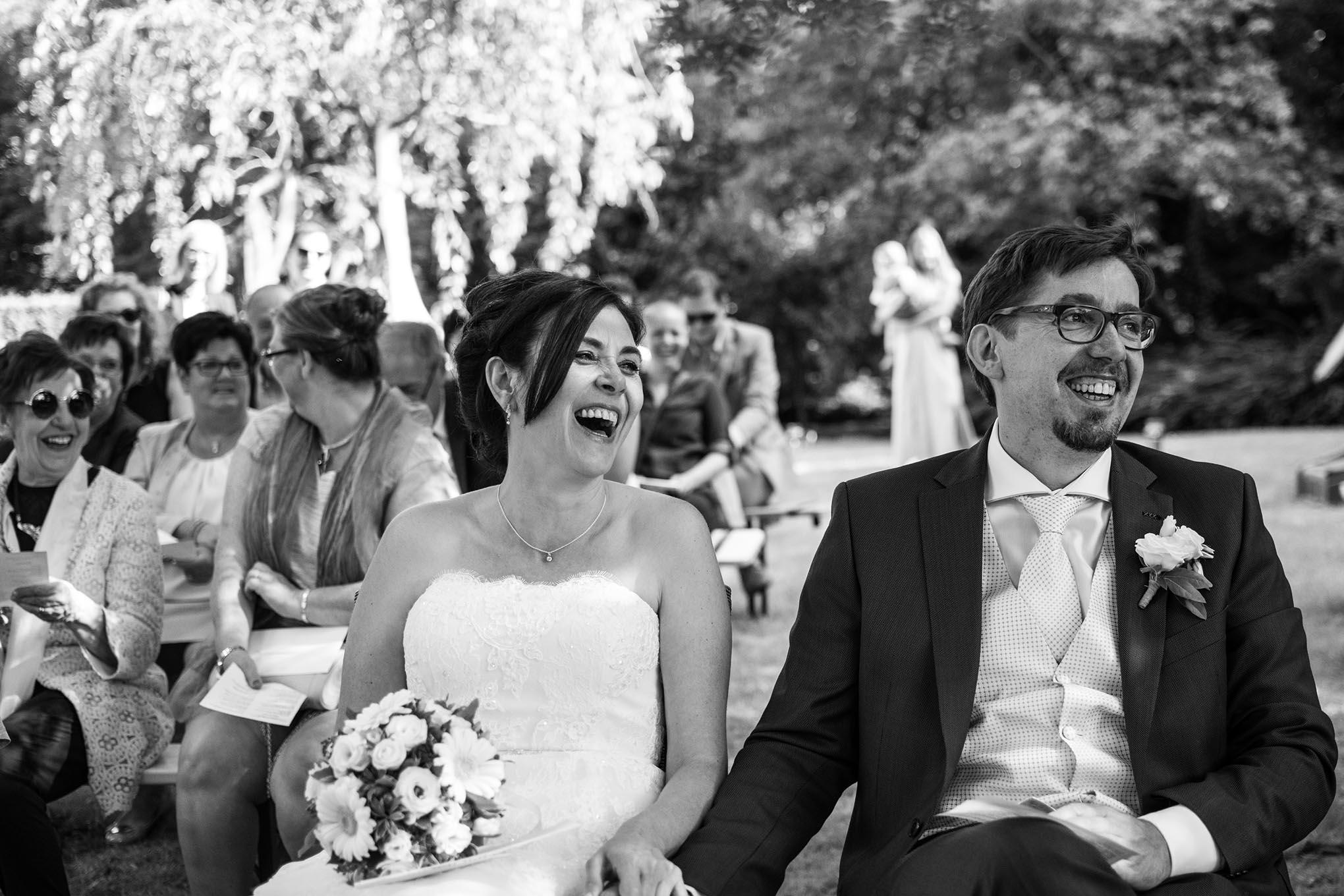 Fotograaf huwelijk Cathy en Koen, koppel lacht tijdens de ceremonie van hun trouw, vrienden en familie kijken toe.