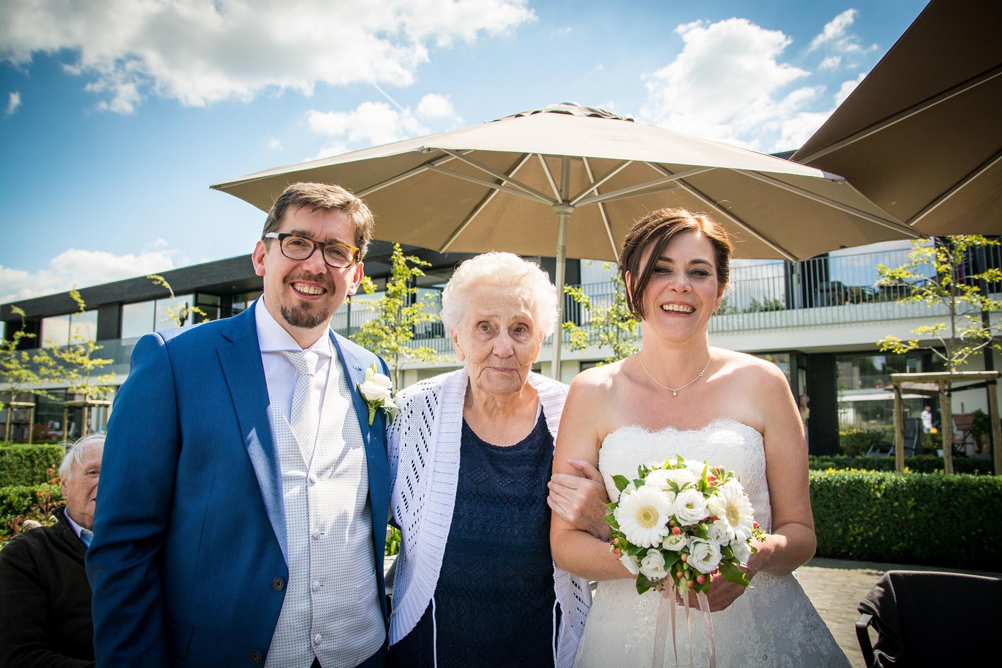 Cathy en Koen staan op hun zonnige trouwdag bij hun grootmoeder in een RVT
