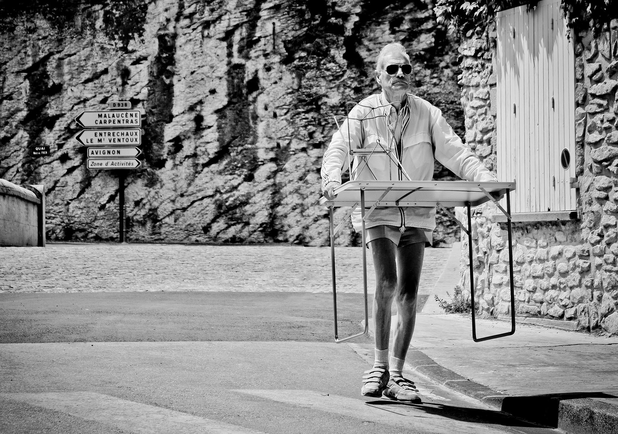 Een oudere man met korte broek en een zonnebril aan kraagt een tafel over straat in het zuiden van Frankrijk.
