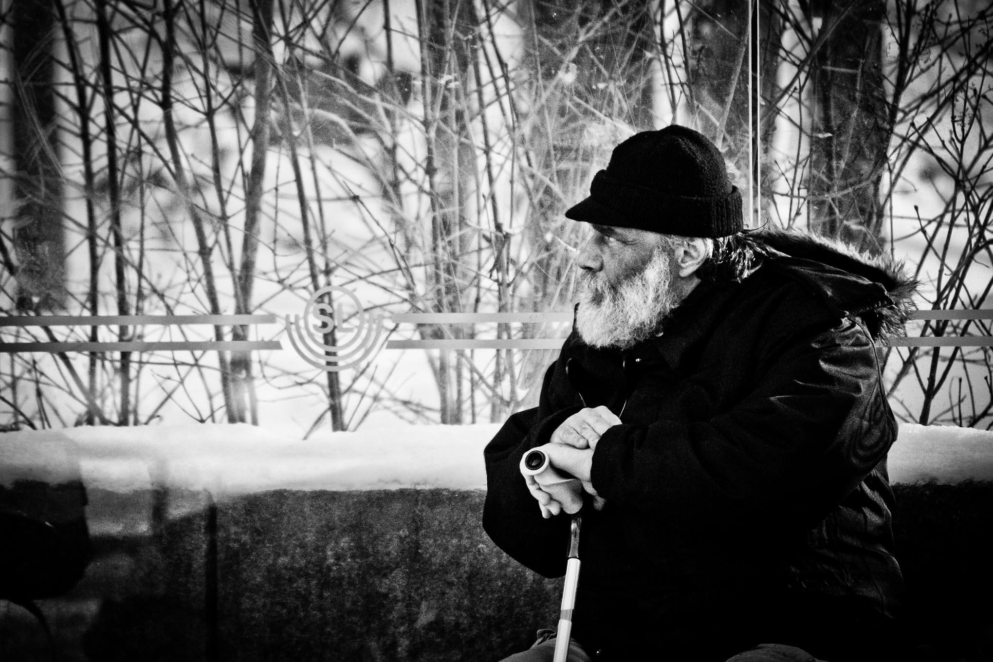 Een man met baard en een kruk wacht in een besneeuwd bushokje op de bus in Stockholm.