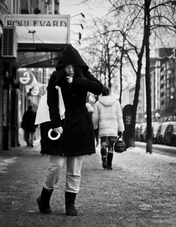 Een Aziatische vrouw doet haar zwarte jas dicht terwijl ze plakband en papieren vast heeft.
