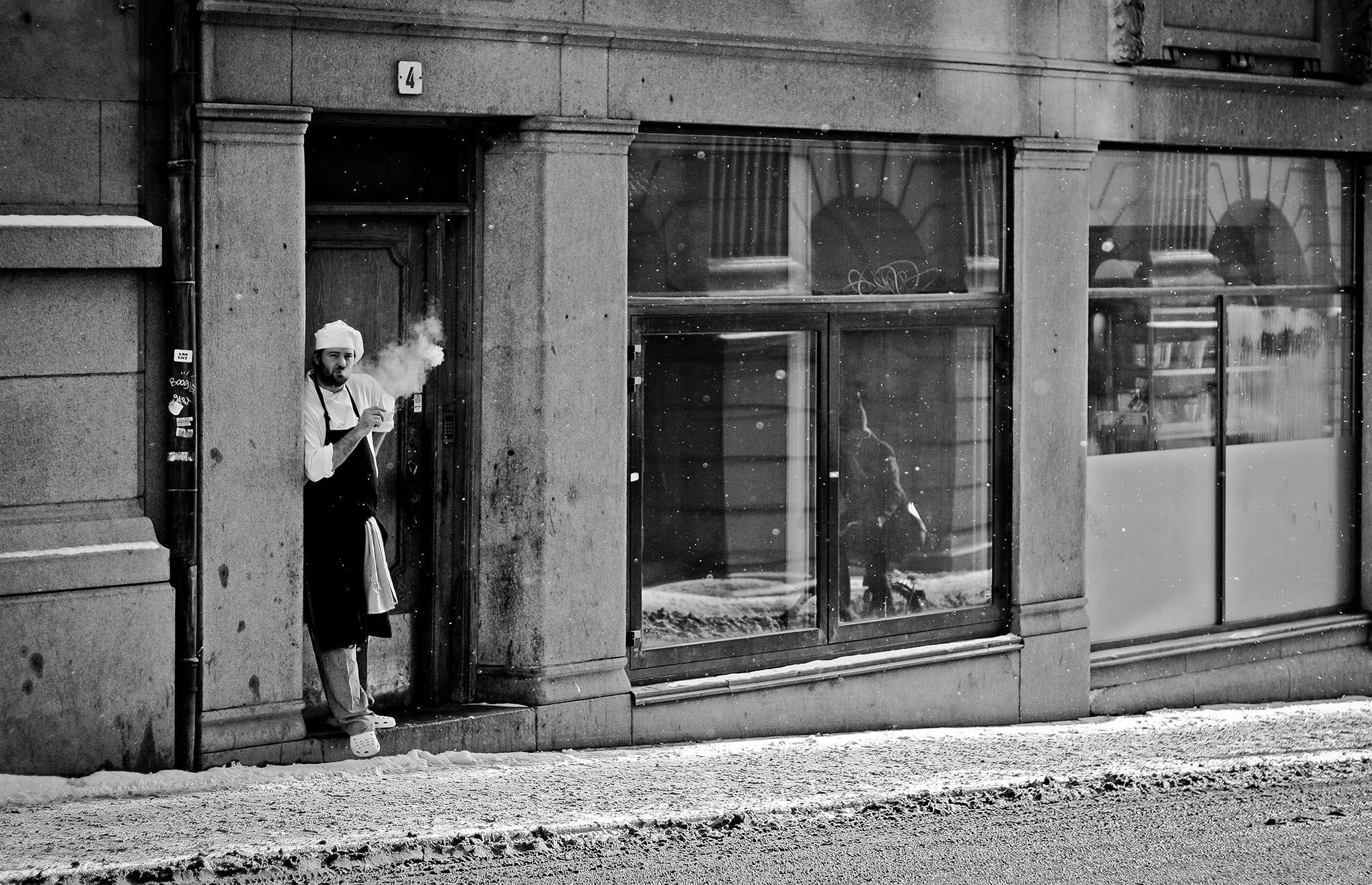 Een kok rookt een sigaret terwijl het sneeuwt in de straten van Stockholm.