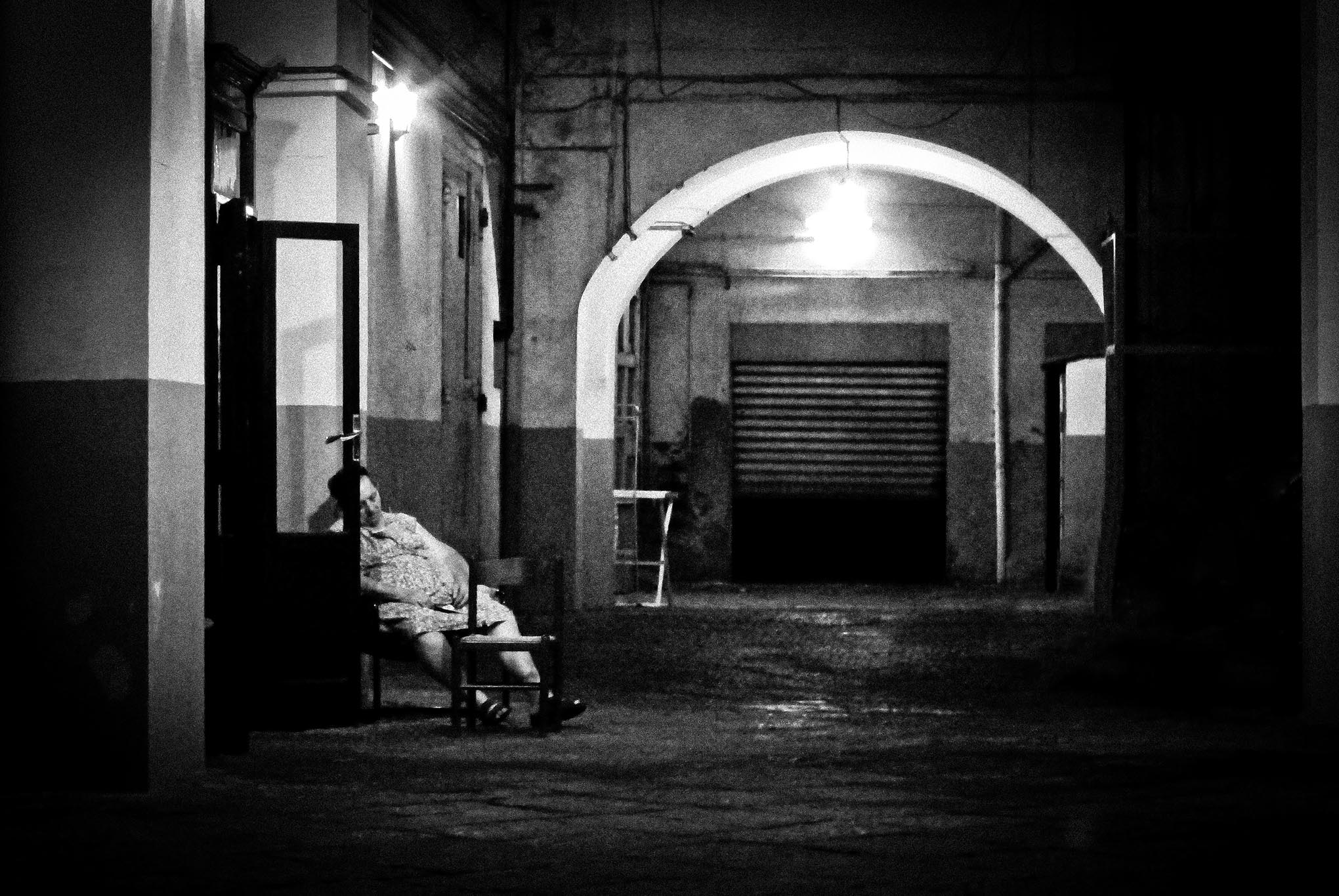 Een vrouw slaapt 's avonds op een stoel in een achterbuurt in Napels.