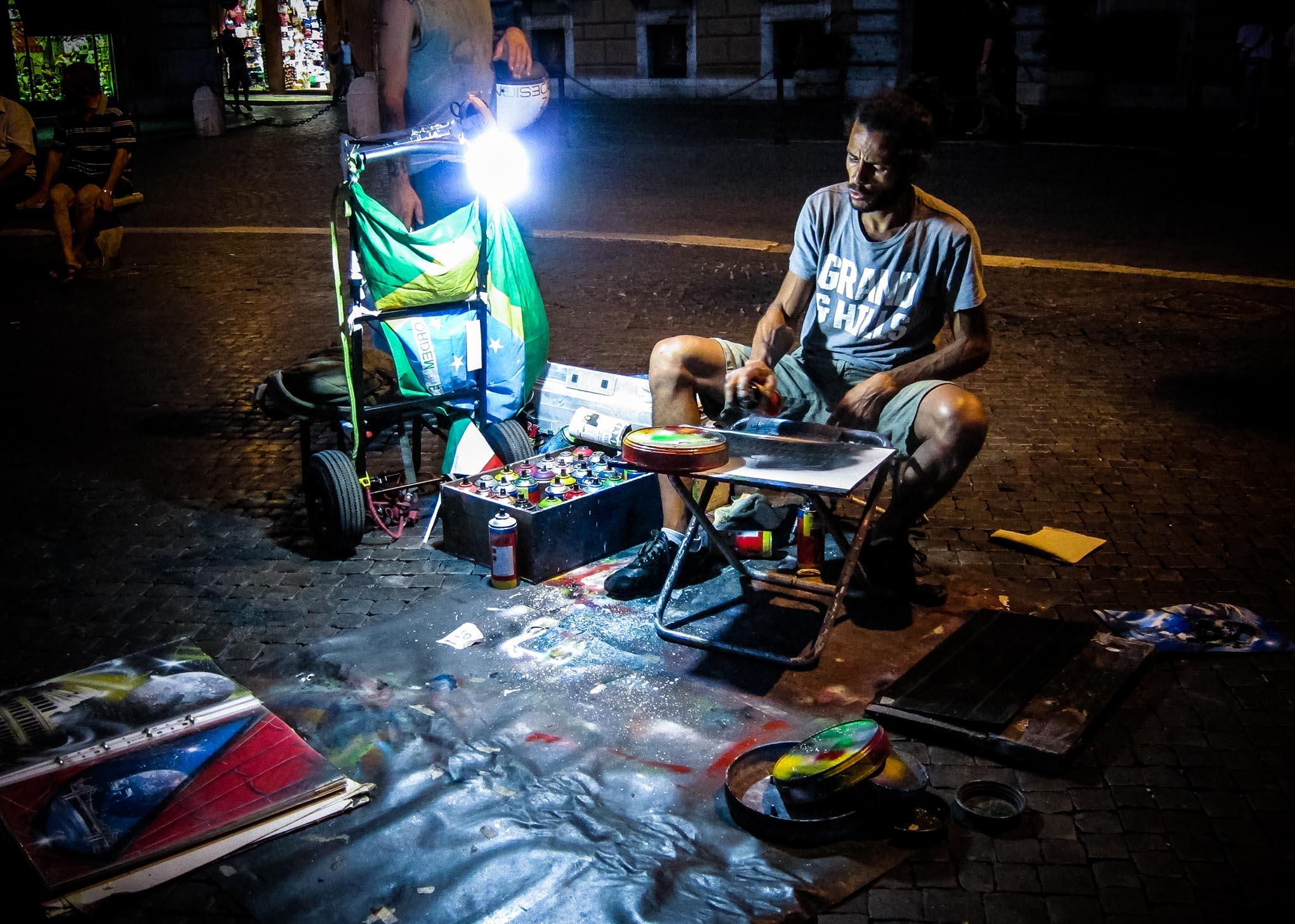 Een straat artiest schildert 's nachts onder een lamp in de straten van Rome.