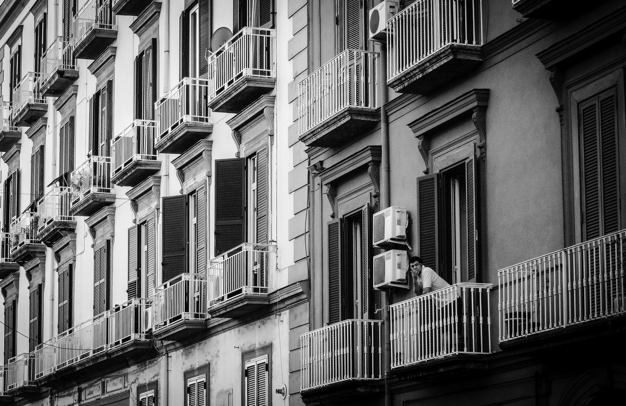 Een man in witte t-shirt leunt over een balkon in een straat in Napels