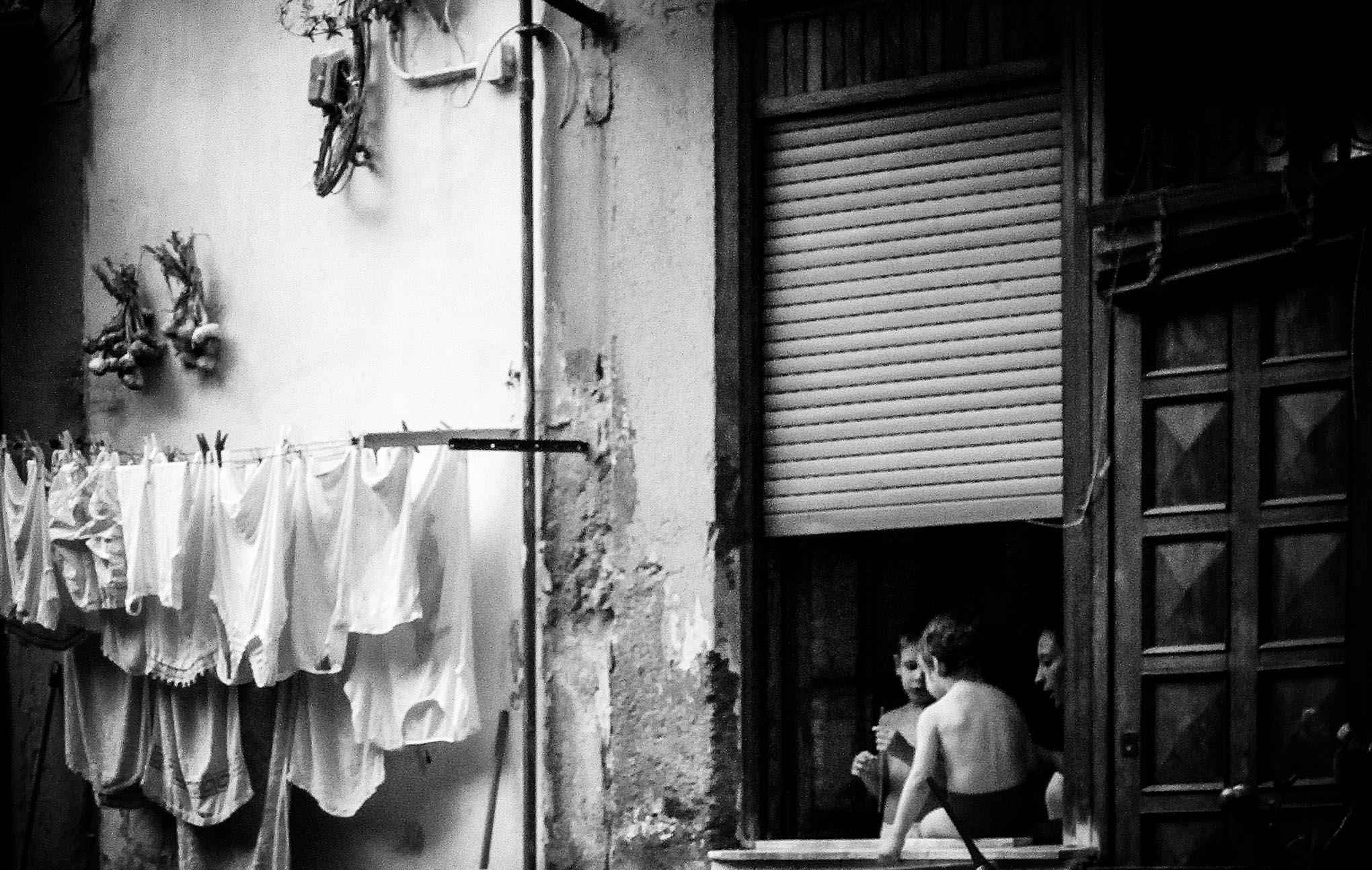 Twee jongens en hun moeden zichtbaar aan een raam in een achterbuurt in Napels.
