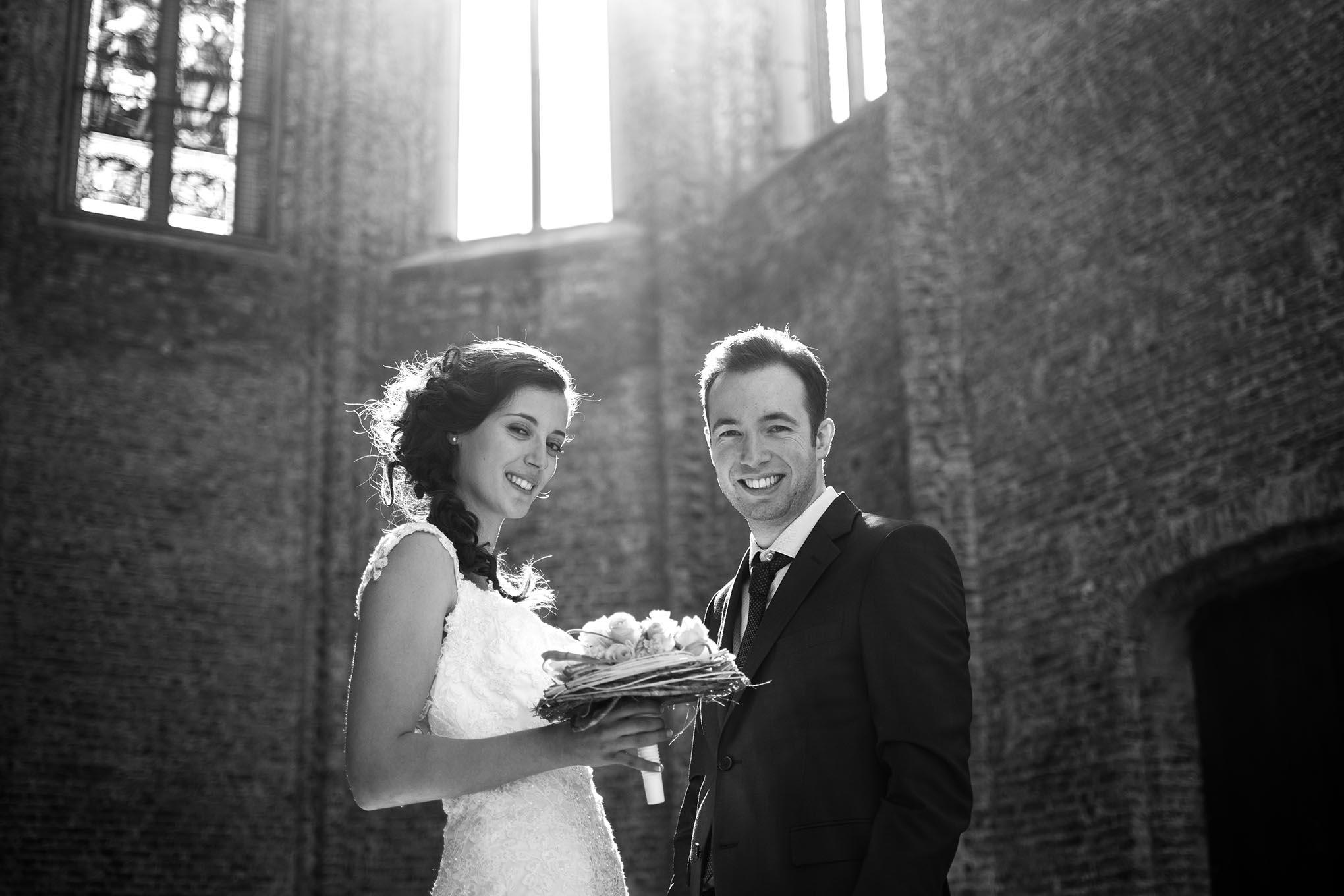 Bruidspaar op hun trouwdag poseert voor een fotoshoot genomen in de kunstkerk van de gemeente Bossuyt.