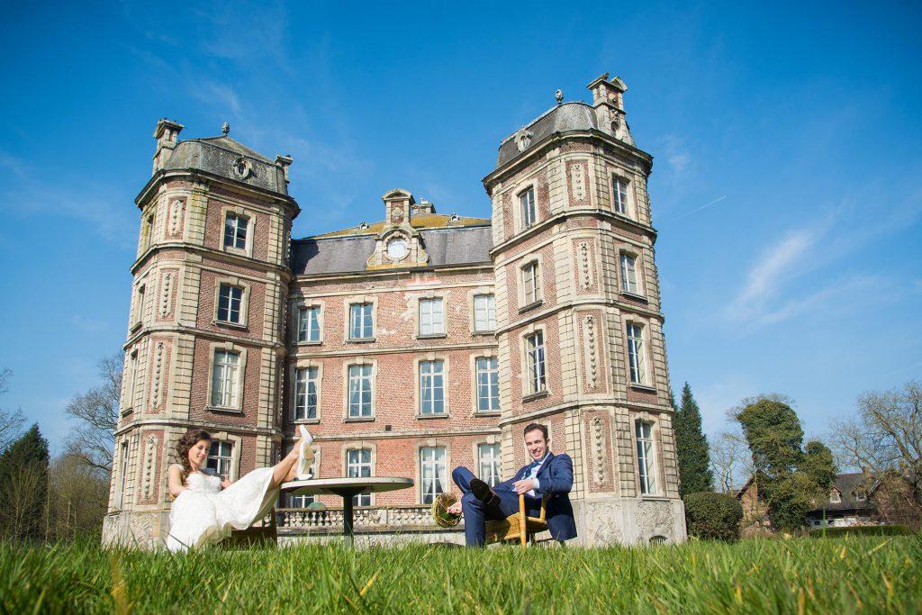 Net getrouwd koppel zit met hun voeten op tafel in de tuin voor het Kasteel van Bossuyt.