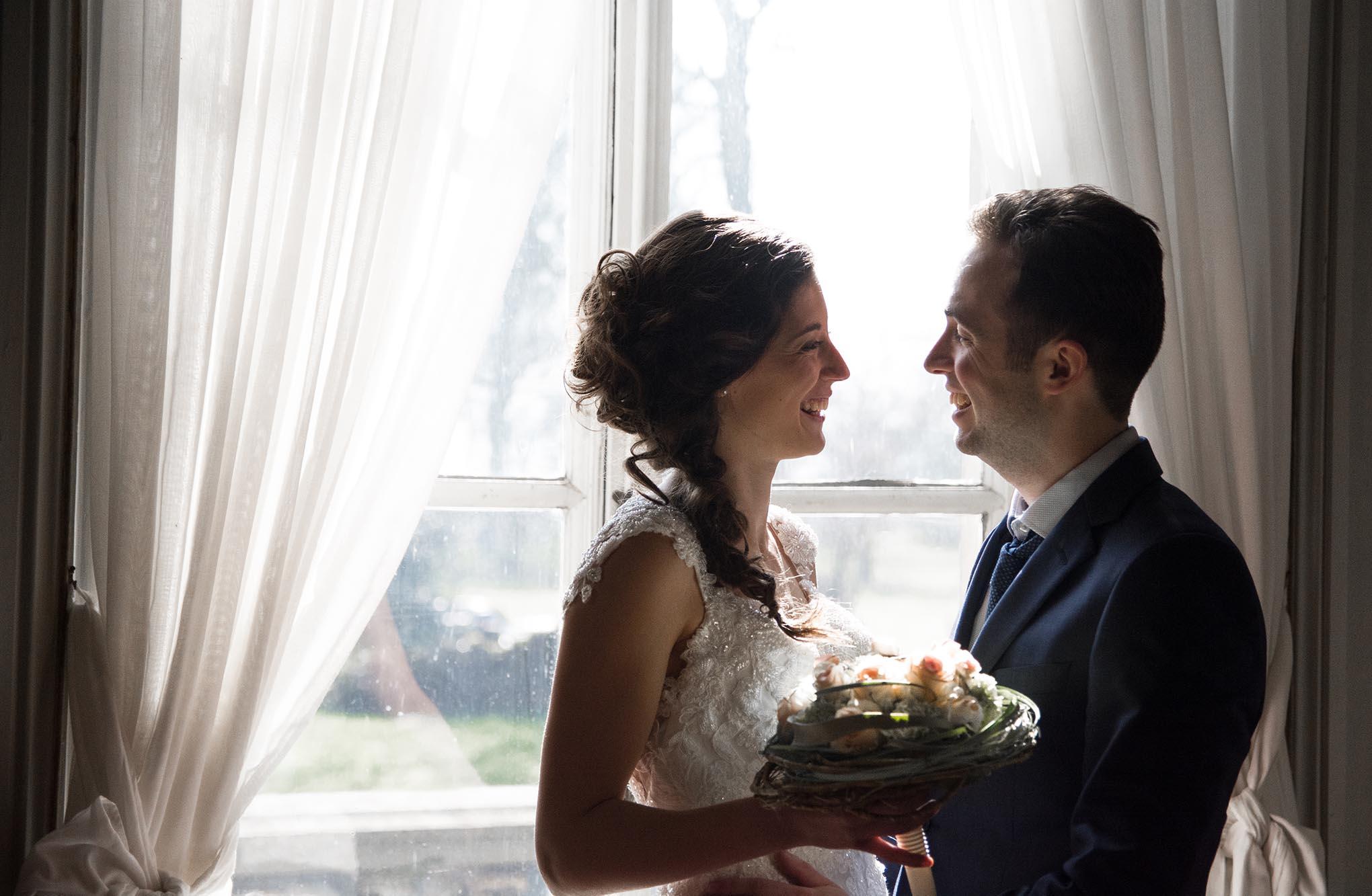 Koppel poseert voor een raam voor de fotoshoot van hun huwelijk in Zwevegem.