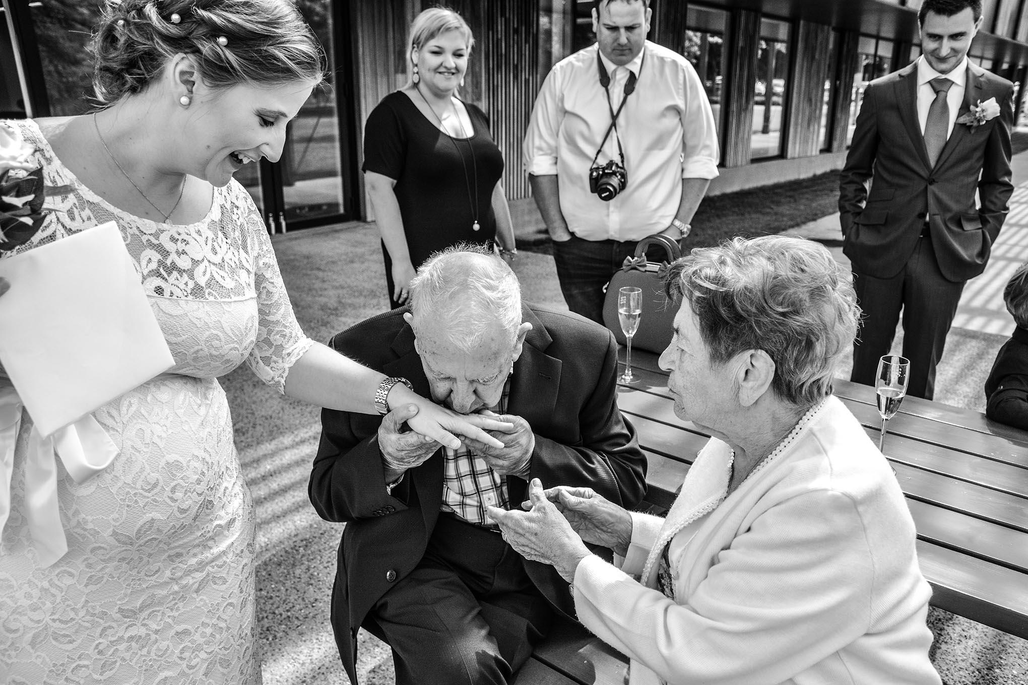 Grootvader kust de ring van de bruid op haar trouwdag, terwijl de grootmoeder haar hand vast houdt.