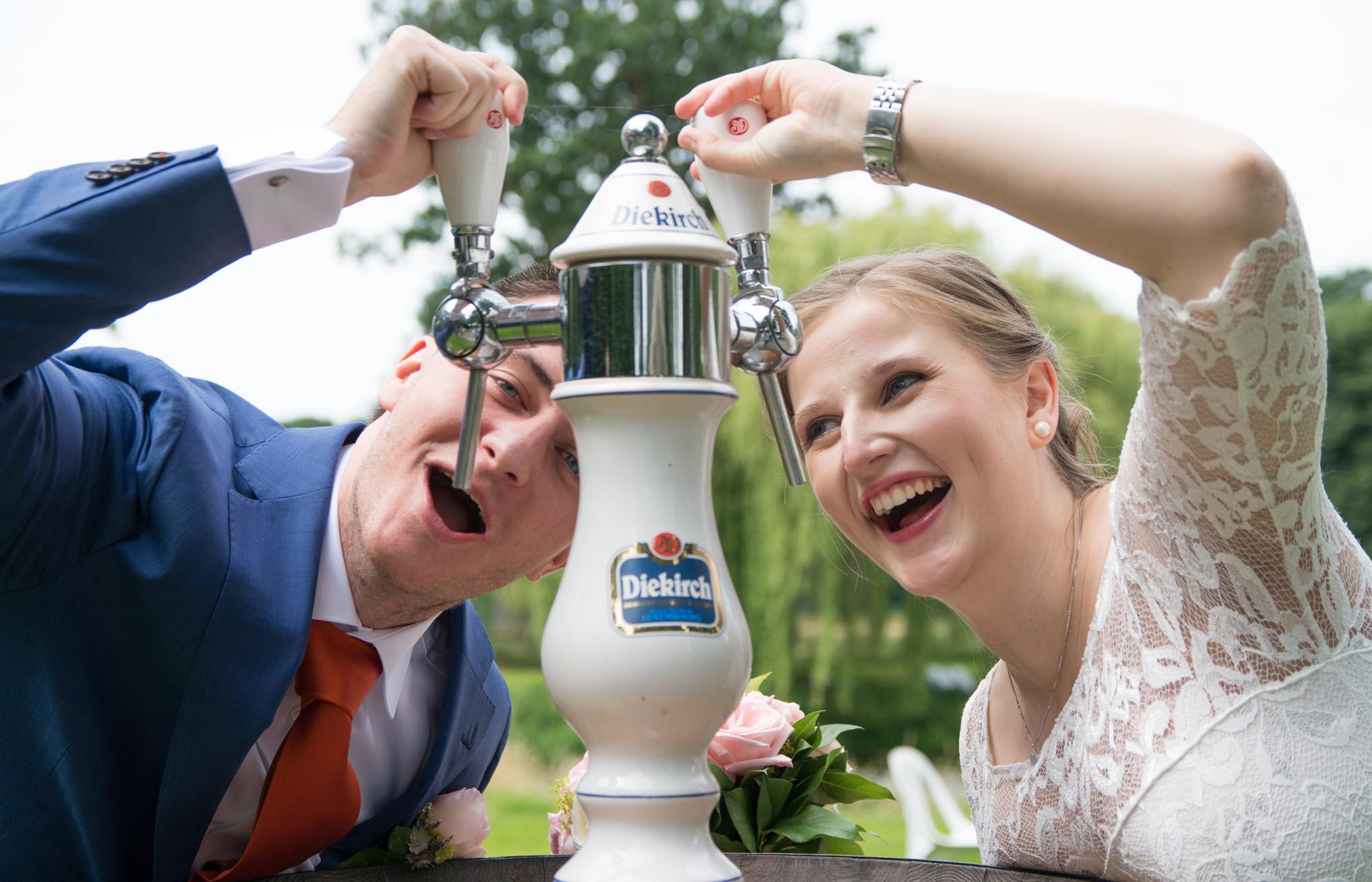 Koppel die net getrouwd is poseert aan een tapkraan in buitenlucht.