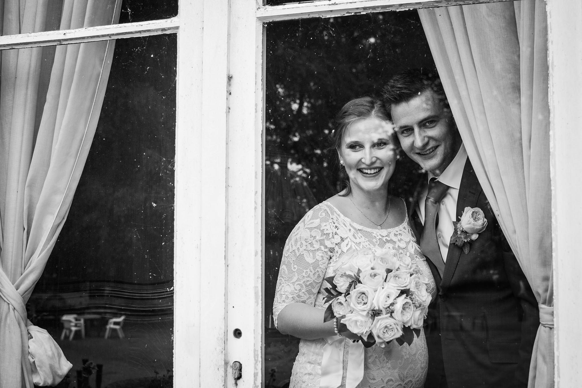 Koppel poseert tijdens hun huwelijk voor een raam in het kasteel van Bossuyt in de regio Kortrijk.