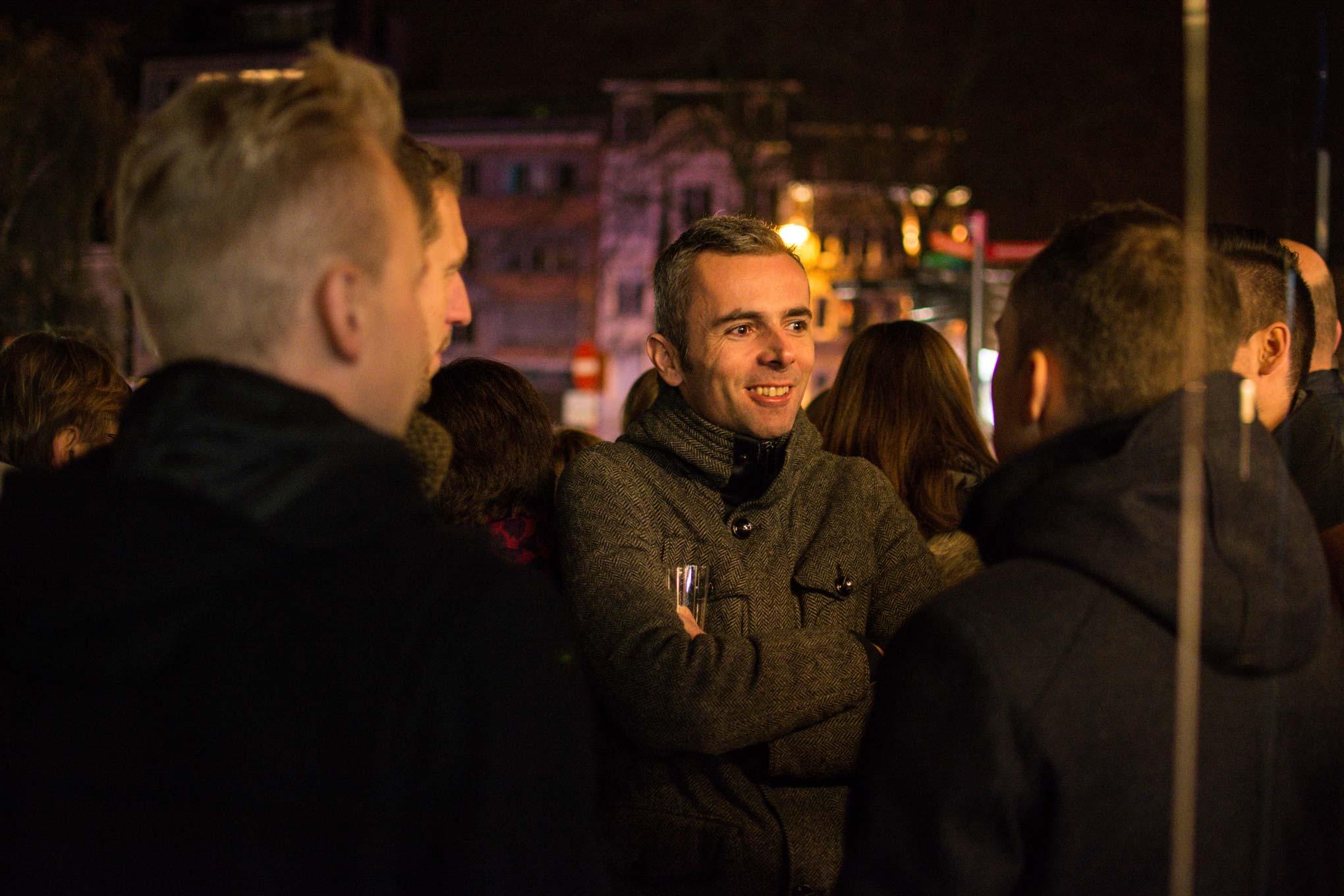 Man op een vernissage op de Graanmarkt in Kortrijk, het is donker.