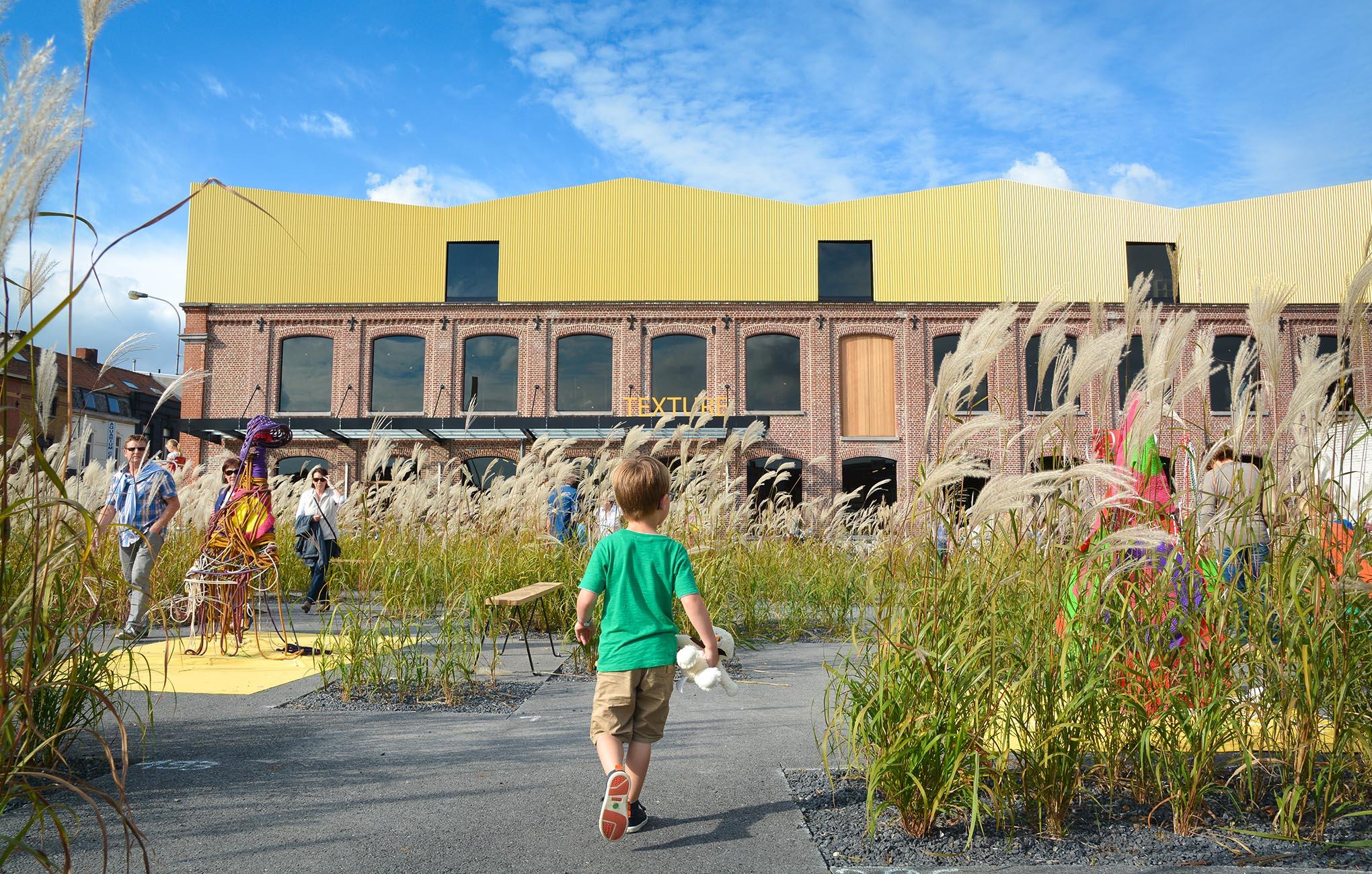 Jongentje met groene t-shirt loopt samen met zijn teddy richting museum Texture op een zomerse dag.